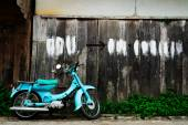 Walls, old wooden houses and a blue motorcycle — Stock Photo