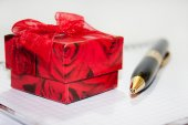 Ring gift box on the notebook with pen — Stock Photo