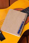 Diary and a used pencil on guitar — Stockfoto