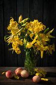 лилии в стеклянной вазе с персиками на старый деревянный фон — Стоковое фото