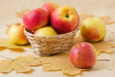 Apples with autumn leaves on the wooden backgraund — 图库照片