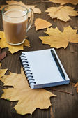 Notebook and cup of coffe with autumn leaves on wooden backgraund — Stock Photo