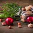 Christmas concept (decoration). Jar with red ball, cone and walnut on rustic wooden background — Stock Photo #58173457