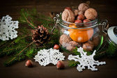 Christmas concept (decoration). Jar  with tangerine, cone and walnut  on rustic wooden background — Stock Photo