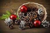 Christmas concept (decoration). Basket with red ball and cone  on rustic wooden background — Stock Photo