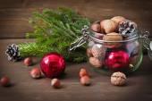 Kerstmis concept (decoratie). Jar met rode bal, kegel en walnoot op rustieke houten achtergrond — Stockfoto