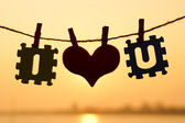 Silhouette of heart and letters hanging on rope — Stock Photo