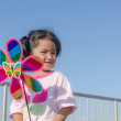 Asian little girl with wind turbine toy in hands — Stock Photo #66360529