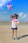 Asian little girl with wind turbine toy in hands — Stock Photo