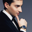 Close-up portrait of handsome elegant young man in suit and white shirt with watch on white background. Fashion model studio shooting. Profile face. Manhood and sexuality. Luxury business style. — Stock Photo #65656249