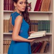 Young beautiful woman in blue long open back dress with lace reading the book in antique living room near vintage bookcase. Romantic style. Tenderness. Fashion model shooting. — Stock Photo #66976049