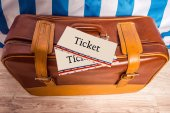 Vintage brown yellow leather bag suitcase with tickets on wooden background. Travel motive. — Stock Photo