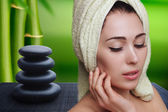 Young beautiful woman in white towel turban on spa background zen stones and bamboo after bath touching her face. Skin care. Beauty and health. Spa treatment. Clear perfect skin. Relax. Massage. — Stock Photo