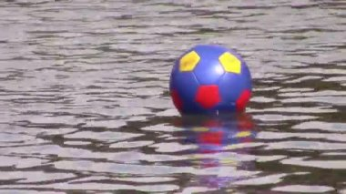 Soccer ball drifting on water — Stock Video