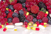 Berries, vitamins and nutritional supplements — Stock Photo