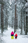 Two children in snow pine forest — Stock Photo