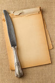 Old knife on yellowed blocknote — Stock Photo