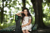 Beautiful girl smiling sitting on the bench in the park — Stock Photo
