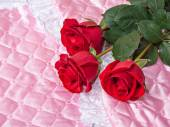 Red roses on pink satin. — Stock Photo