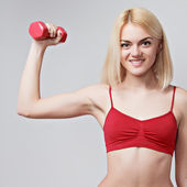 Girl with a sports figure does exercises with dumbbells — Stock Photo