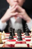 Muž na bílé tričko černé barvy hrají šachy si pro strategii b — Stock fotografie