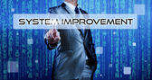 Business man with digital background pressing on button system improvement — Stock Photo