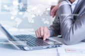 Close up of business man typing on laptop computer with technolo — Stock Photo
