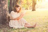 Pretty girl playing electronic pad in park, vintage style — Stock Photo