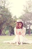 Ouvir música através do small talk a vintage sente-se garota no parque — Fotografia Stock