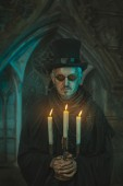 Scary man with candles in the candelabra. — Stock Photo