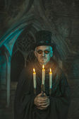 Evil sorcerer with a candelabra in hand. — Stock Photo