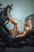 Girl shakes legs trainer in the gym. — Stock Photo