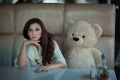 Sad girl at the table with a toy bear. — Stock Photo