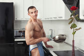 Male bodybuilder holding a frying pan. — Stock Photo