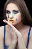 Girl crying yellow blue tears. — Stock Photo