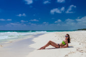 Young cute woman lying and getting sun at tropical white sand beach — Stock Photo