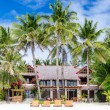 Luxury villa and palm trees around at beautiful exotic white sandy beach — Stock Photo #66990459