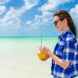 Young cute woman with coconut at tropical sandy beach in the Caribbean sea — Stock Photo #66990491
