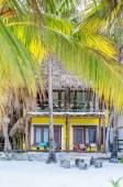 Tropical villa view through palm trees at exotic sandy beach — Stock Photo