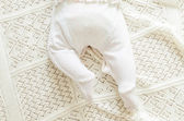Tiny little newborn baby's feet in spotted romper suit on woolen — Stock Photo