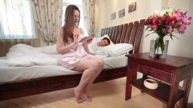 Wife using tablet and waking up husband — Vídeo de stock