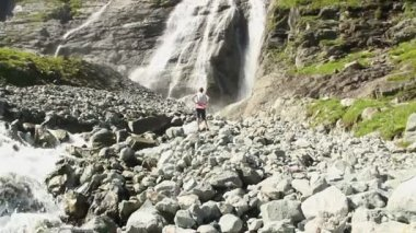 Female tourist walking at the foot of waterfall — Stock Video