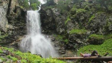 Tourist having rest near mountain waterfall — Stock Video