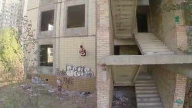 People climbing the wall of abandoned building — Vídeo Stock