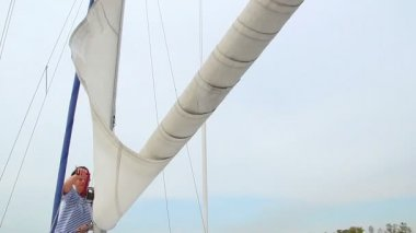 Sailor lifting the sail on yacht — Stockvideo