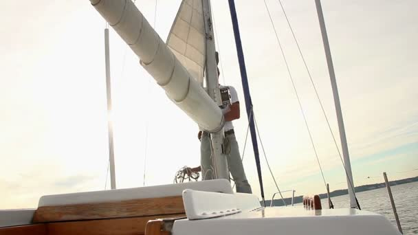 Sailor putting up sails on yacht — Vidéo