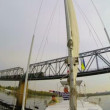 Yacht sailing under railway bridge — Stock Video #64861195