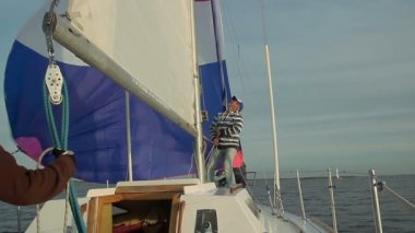 Captain putting up mainsail — Stock video