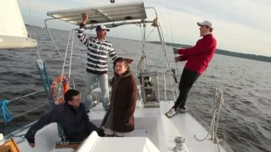 Yachting, four people crew on sailing boat, captain rings bell — Stockvideo