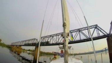 Yacht sailing under railway bridge — Stock Video